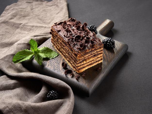 Pedaço de bolo de chocolate com amoras e hortelã em fundo marrom