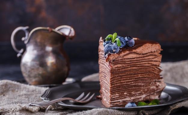 Pedaço de bolo de chocolate de panquecas de chocolate com glacê, com mirtilos
