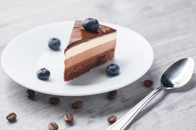 Pedaço de bolo de chocolate delicioso com suflê de três cores diferentes em foco suave. estilo tiramisu com cor branca e marrom.