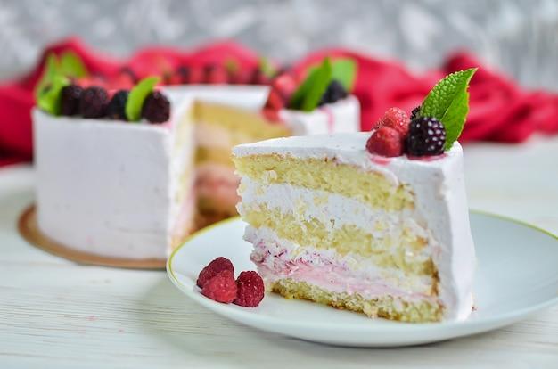 Pedaço de bolo de iogurte de iogurte de biscoito fresco branco com framboesas frescas e amoras