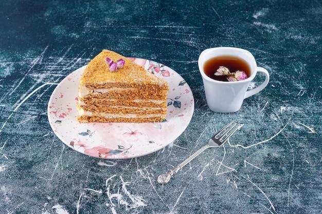 Pedaço de bolo de mel com colher e uma xícara de chá colocado sobre uma superfície colorida.
