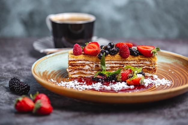 Pedaço de bolo de mel decorado com morango, groselha preta e framboesa