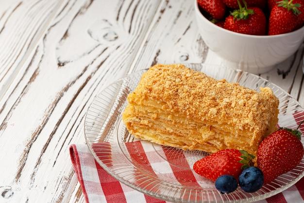 Pedaço de bolo de mel russo medovik servido com frutas