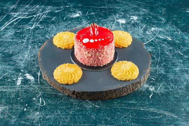 Pedaço de bolo de morango com biscoitos na peça de madeira.