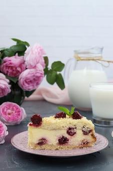 Pedaço de bolo de queijo cottage com cerejas em um fundo escuro e jarro com leite. formato vertical