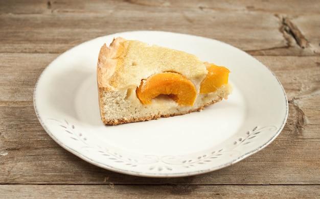 Pedaço de bolo de queijo de pêssego aberto em chapa branca na mesa de madeira