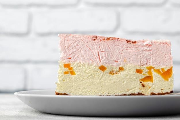 Pedaço de bolo de queijo em prato branco contra parede de tijolos