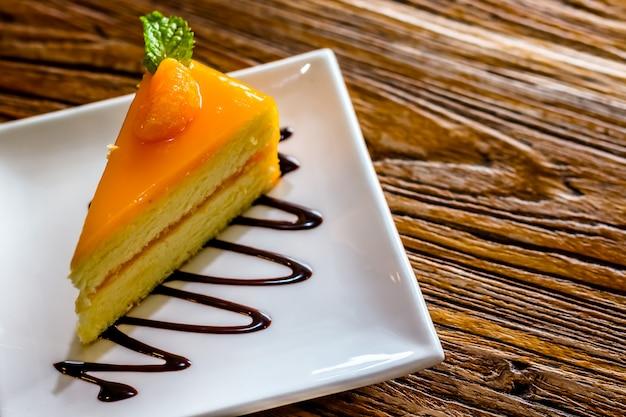 Pedaço de bolo de queijo laranja na placa sobre a mesa de madeira