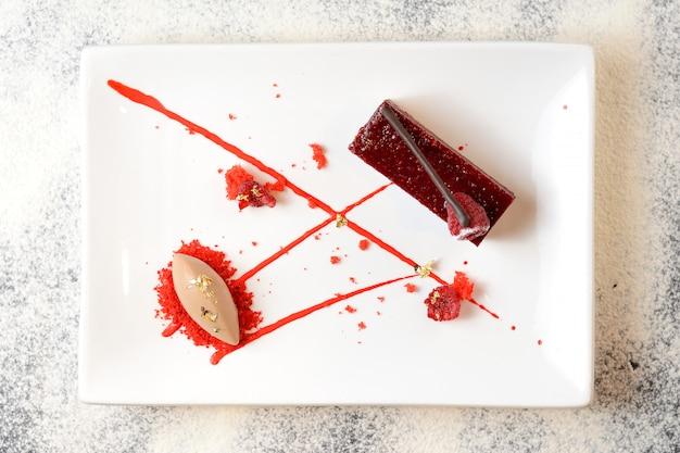 Pedaço de bolo de veludo vermelho com framboesas em um prato branco
