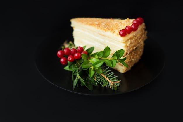 Pedaço de bolo decorado com árvore de natal e frutas vermelhas em uma superfície preta