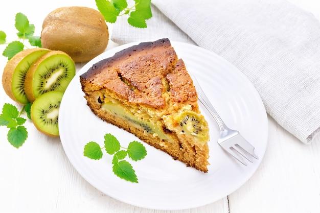 Pedaço de bolo doce com kiwi e mel, hortelã e um garfo em um prato, um guardanapo em uma placa de madeira branca de fundo
