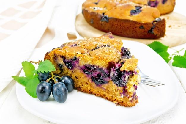 Pedaço de bolo doce com uvas pretas e mel, hortelã e um garfo em um prato, uma toalha no fundo claro de madeira