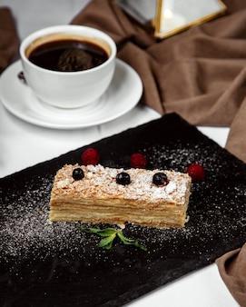 Pedaço de bolo napoleão decorado com açúcar em pó, servido com chá preto