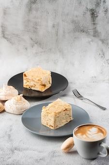 Pedaço de bolo napoleon na placa azul no fundo de mármore, fim acima da vista. sobremesa tradicional do millefeuille com massa folhada e creme, espaço da cópia. foto vertical. foto para menu de padaria.