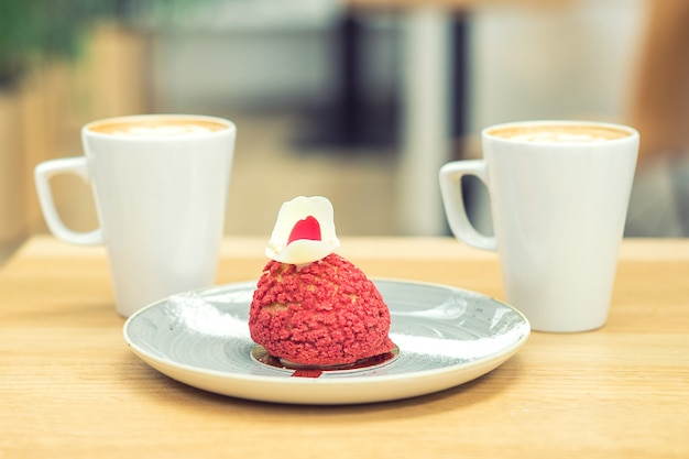 Pedaço de bolo vermelho com duas xícaras de café na mesa de madeira no café.