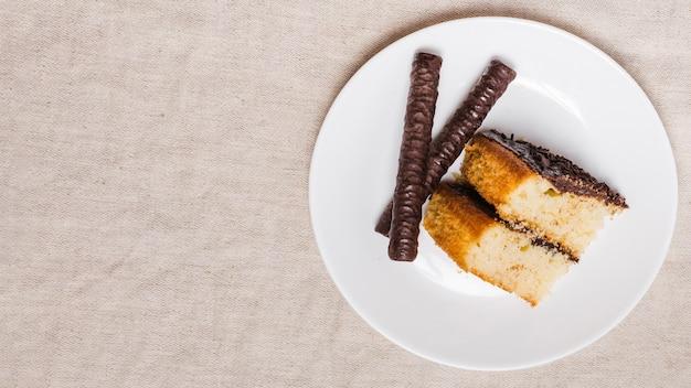 Pedaço de bolo vista superior com vara de chocolate