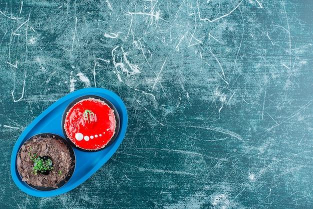 Pedaço de bolos de chocolate e morango na placa azul.