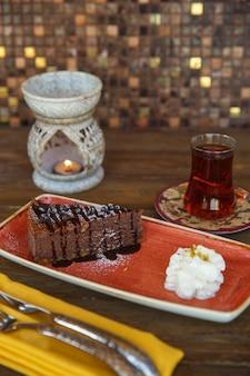 Pedaço de brownie de chocolate servido com creme e chá