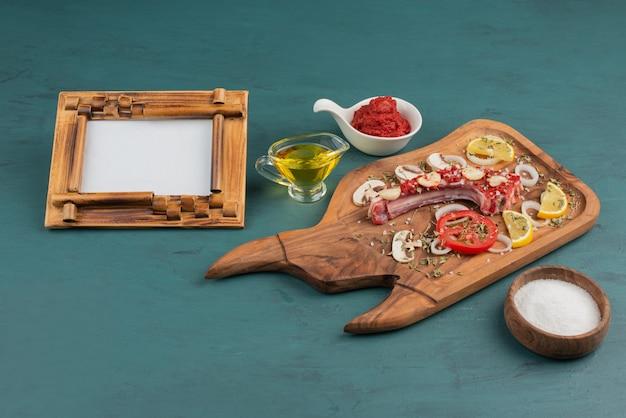 Pedaço de carne crua com legumes e moldura na mesa azul.