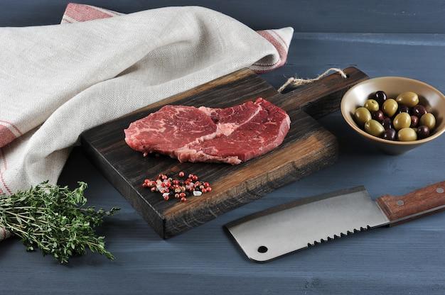 Pedaço de carne crua em uma tábua de madeira, uma faca para carne, azeitonas e tomilho