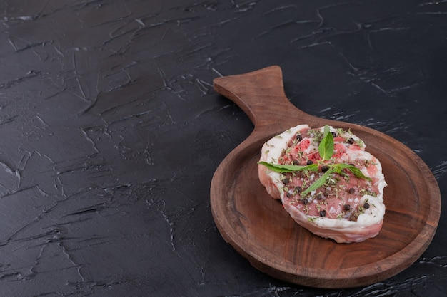 Pedaço de carne crua na placa de madeira decorada com hortelã fresca em fundo escuro.