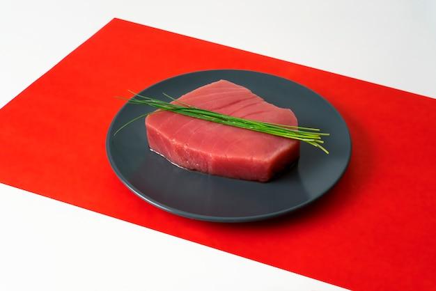 Pedaço de carne de atum cru com cebolinha na toalha de mesa vermelha
