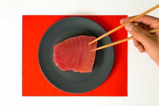 Pedaço de carne de atum cru e mão com pauzinhos