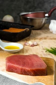 Pedaço de carne de atum na placa de madeira com cozinha