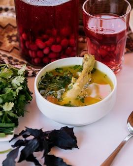 Pedaço de carne dentro da sopa de caldo com ervas e um copo de composto de frutas vermelhas.