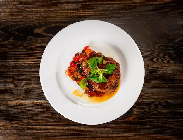 Pedaço de carne suculento com legumes cozidos e manjericão e molho de creme em um prato branco.