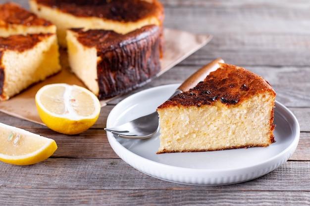 Pedaço de cheesecake basco de san sebastian no prato sobre uma mesa de madeira com limão e uma xícara de chá