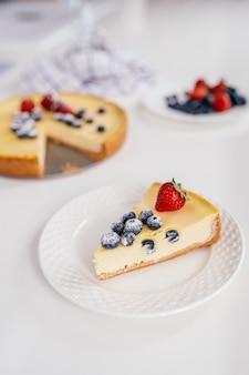 Pedaço de cheesecake caseiro de baga de inverno de natal em um prato branco.