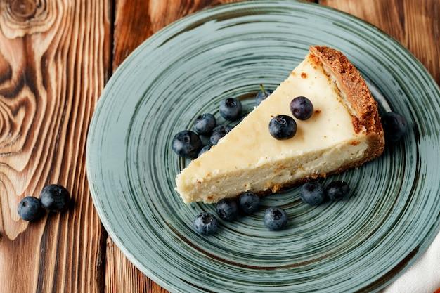 Pedaço de cheesecake clássico no prato verde close-up