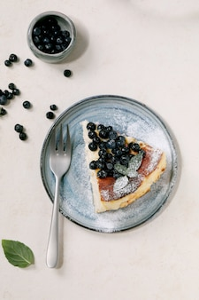 Pedaço de cheesecake macio de mirtilo caseiro assado em um prato de cerâmica