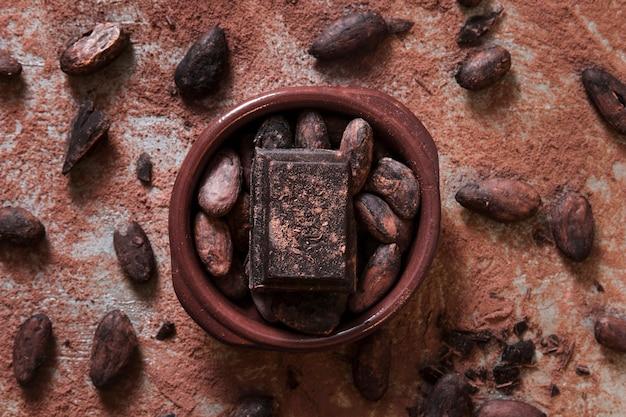 Pedaço de chocolate e grãos de cacau na tigela