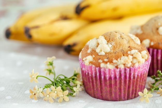 Pedaço de crumble de banana e cupcake ou muffin de gergelim em um mini copo rosa na mesa com espaço de cópia