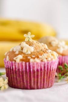 Pedaço de crumble de banana e cupcake ou muffin de gergelim em um mini copo rosa na mesa na vertical