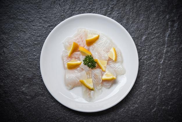 Pedaço de filé de peixe cru fresco no prato branco com limão fundo escuro pangasius dolly peixe carne