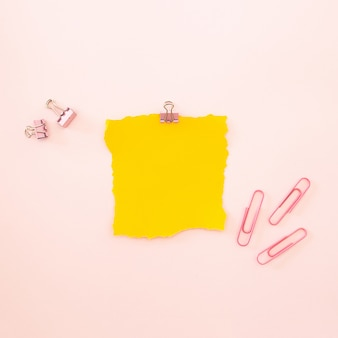 Pedaço de folha amarela sobre um fundo rosa