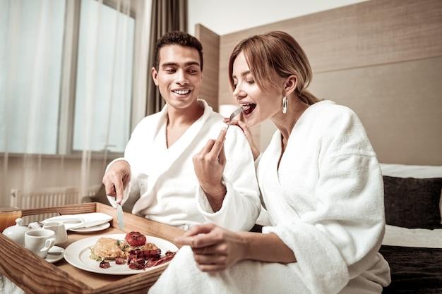 Pedaço de linguiça. namorado de olhos escuros compartilhando um pedaço de salsicha com sua amada enquanto toma o café da manhã no hotel