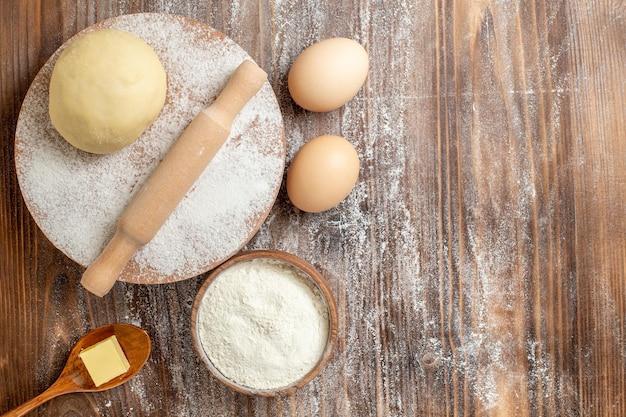 Pedaço de massa crua com farinha e ovos na mesa de madeira farinha para assar a massa