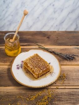 Pedaço de mel na placa branca de madeira com pólen de lavanda e abelha na mesa de madeira