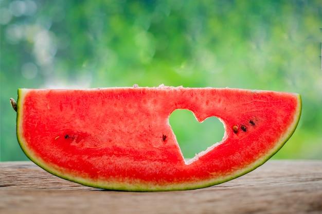 Pedaço de melancia com coração no pano de fundo de vegetação. configuração plana