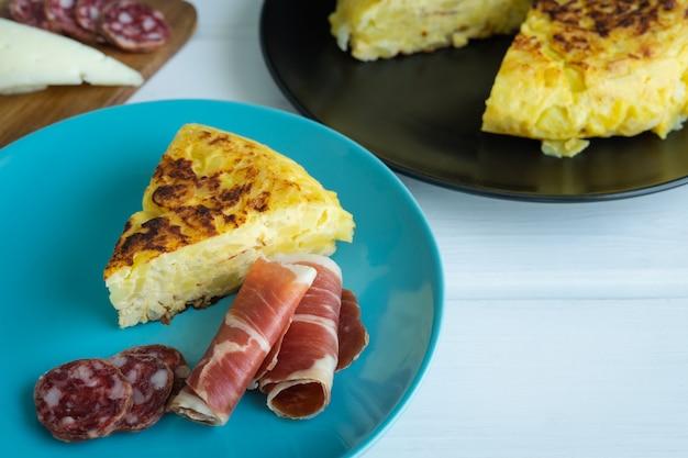 Pedaço de omelete de batata com presunto e salsicha em um prato azul com uma taça de vinho em uma mesa branca