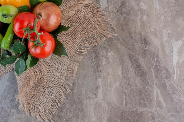 Pedaço de pano sob uma pilha de pimentão, cebola, tomate vermelho, tomate verde, pepino, cebola roxa e folhas em mármore.