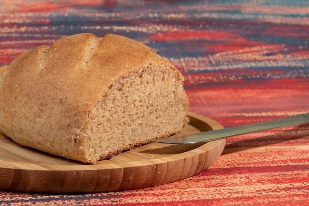Pedaço de pão caseiro cortado em bandeja de bambu sobre mesa rústica