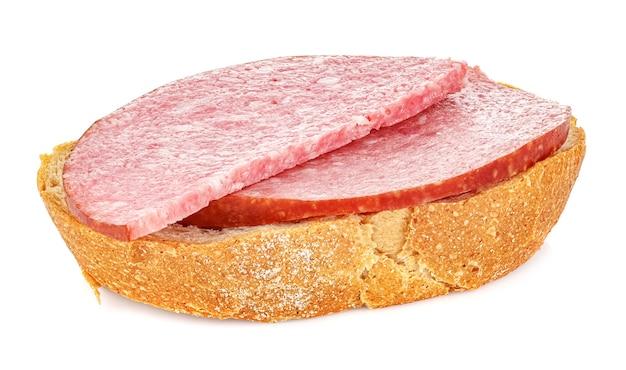 Pedaço de pão de centeio fresco com duas fatias de linguiça defumada no branco