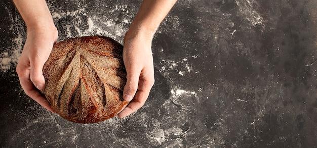 Pedaço de pão inteiro redondo nas mãos do padeiro em fundo cinza escuro com espaço livre para texto, banner web para padaria. foto de alta qualidade