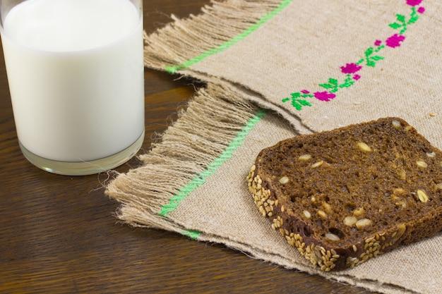 Pedaço de pão preto com sementes de girassol, polvilhe com sementes de gergelim. guardanapos de mesa em cânhamo. um copo de leite