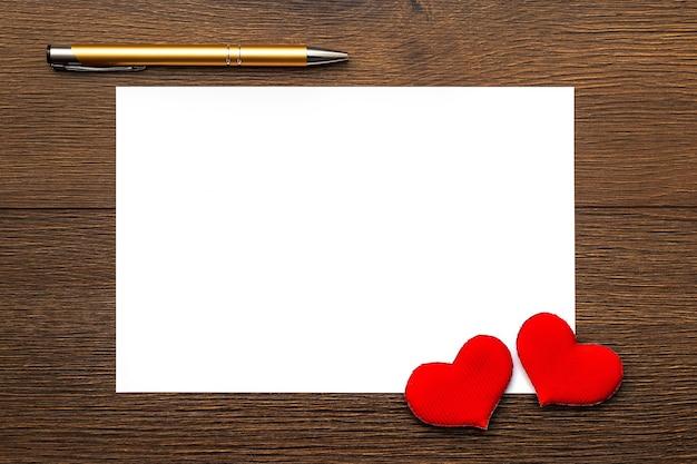 Pedaço de papel branco para colar texto, corações e caneta na madeira